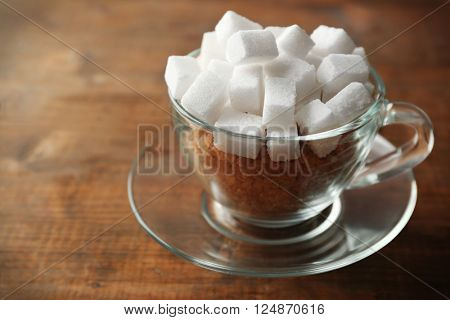 Glass cup with lump and brown sugar on wooden background