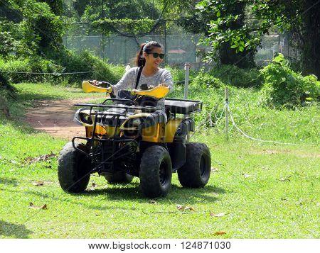 Young woman having fun riding ATV all-terrain vehicle