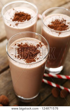 Glasses of chocolate milkshake on wooden table closeup