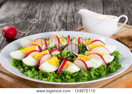Delicious Spring onion eggs radish salad in a white dish on an old rustic wooden table horizontal close-up