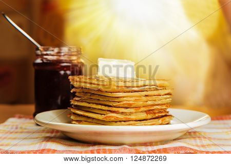 Pancakes with butter and jam on the table in front of a window with sunlight