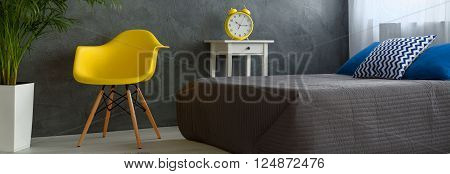Panorama of a modern bedroom with grey stucco wall, grey-covered bed and yellow designer chair