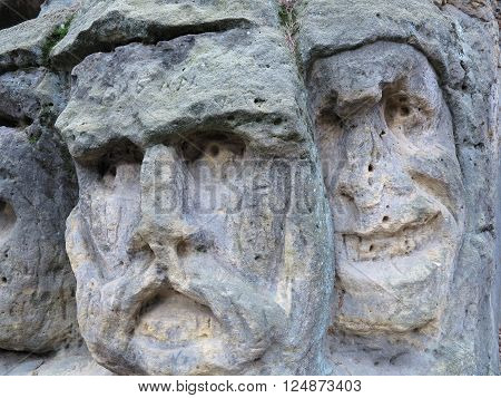 Scary Stone Heads - rock sculptures of giant heads carved into the sandstone cliffs in the pine forest