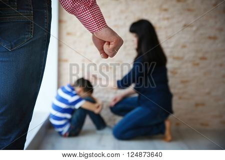 Father fist as punishment and little boy with mother sitting on floor indoors