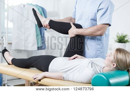 Male chiropractor stretching female leg during rehabilitation