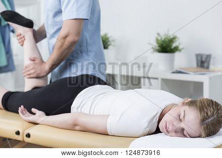 Close-up of masseur massaging female customer's leg