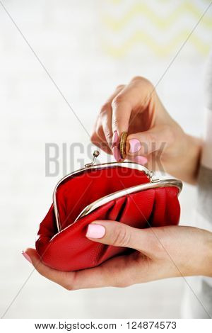 Young woman getting euro coin from purse