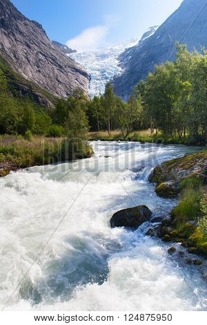 Norway. Summer day in the valley of a glacier Briksdal. A stream of thawed snow against mountains and a glacier