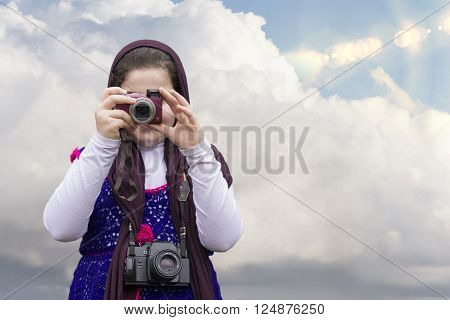 Young Little Girl Is Taking Photograph by Point and Shoot Digital Camera In front of Blue Sky with Clouds. An old Analogue Camera Strapped on Her Neck. Selection Path Included.