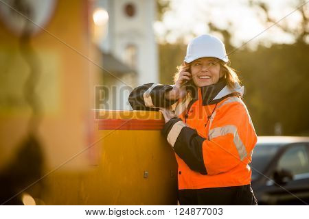 Senior woman engineer helmet wearing protective wear calling phone in work