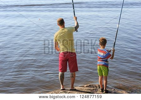 Father and son lake fishing together. They're using telescopic fishing rods fishing line floats and baited fishing hooks. Man has tattoos.