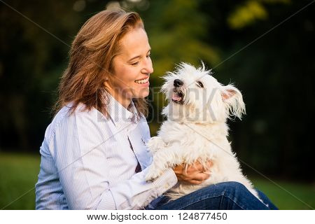 Senior woman playing with her cute white dog outdoor in park