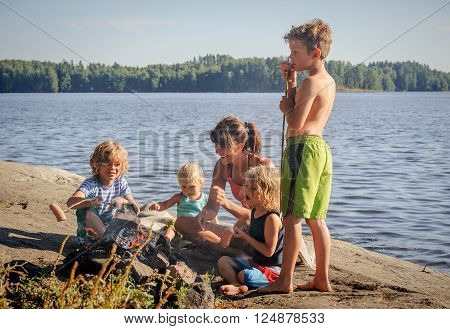 Mother with four children grilling sausages over a camp fire beside a lake. The sausages are stuck onto wooden steaks gathered from the forest.