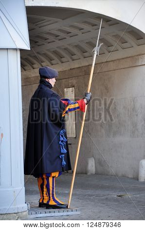 VATICAN CITY - MARCH 13 2016: Papal Swiss guard standing in the front of Saint Peter basilica in Vatican Rome