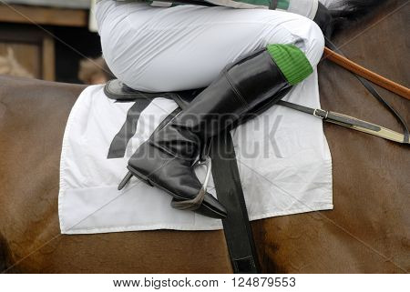 Jockey's boot in the stirrup on a racehorse.