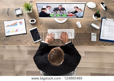 Young Businessman Attending Video Conference On Computer At Office