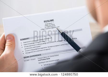 Close-up Of A Businessman Analyzing Resume