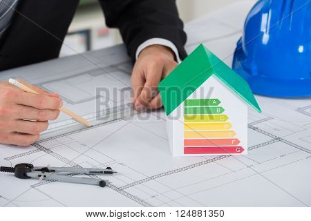 Architect Working On Blue-print Near House Model Showing Energy Efficiency In Office