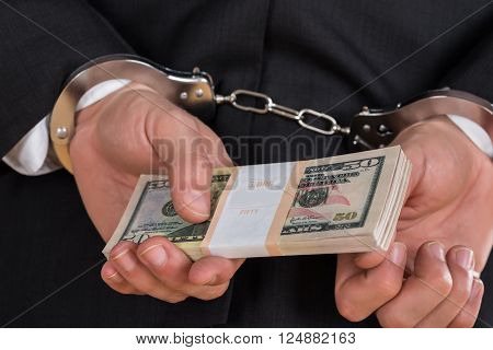 Close-up Of Businessman In Handcuffs Holding Dollars For Bribe
