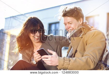 Young Smiling couple having fun with mobile phone / smartphone sitting outside in a park -  analog image shot with vintage soft lens
