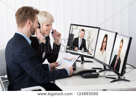 Two Businesspeople Video Conferencing On Desk With Multiple Computer