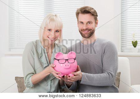 Happy Couple Sitting On Sofa Holding Piggybank At Home
