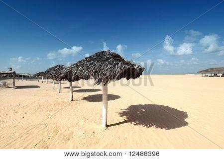 umbrella in desert under blue sky