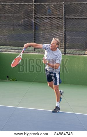 Senior age man showing perfect follow through on serve.