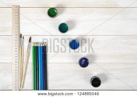 Top view of three paint brushes and a centimeter ruler with colorful gouache containers on a light wooden background.