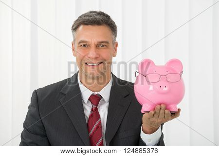 Mature Happy Businessman Holding Piggy Bank In Office