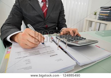 Close-up Of Businessman Hand Calculating Invoice Using Calculator At Desk In Office