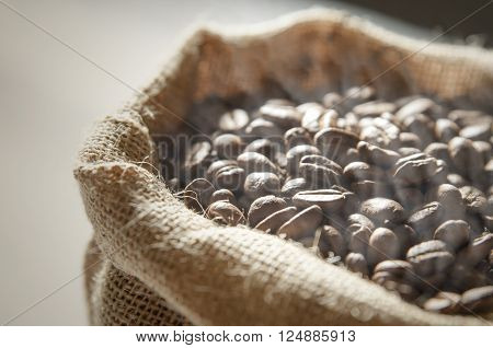 Close up coffee beans in jute bag on wooden table
