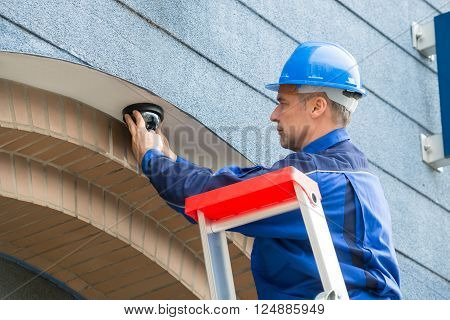Male Technician Installing Camera Standing On Stepladder