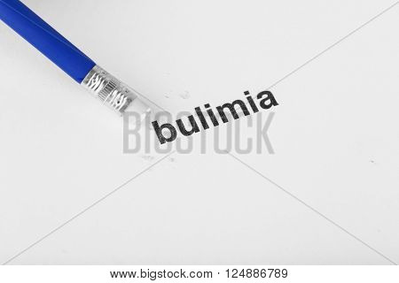Bulimia word with pencil eraser on white paper background