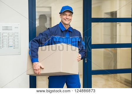 Deliveryman Standing Near Door Holding Box
