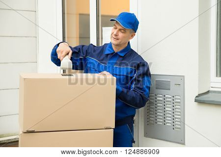 Mature Delivery Man Scanning Cardboard Boxes With Barcode Scanner
