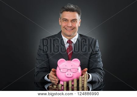 Mature Happy Businessman Sheltering Coins And Piggybank At Desk ** Note: Shallow depth of field