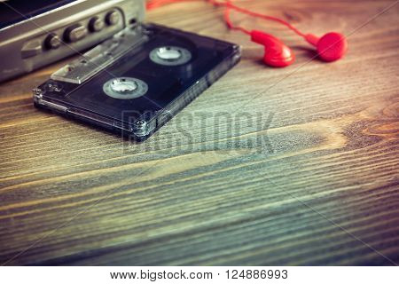 Audio cassette tapes and red earphones and player over wooden table vintage style selective focus