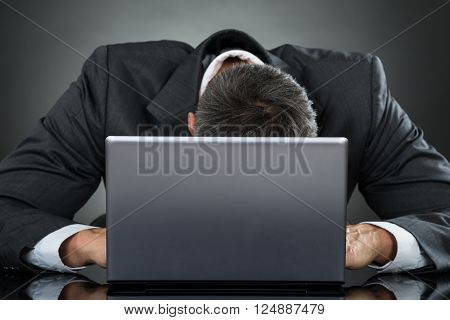 Stressed Businessman Leaning On Laptop At Desk Against Gray Background