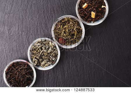 Four bowls with different types of tea: black and green, with fruits are standing on black stone textured backgroung. Place for your text.