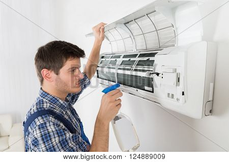 Male Technician Cleaning Air Conditioner