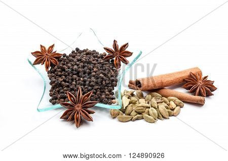 On an white background is there Anise star and cardamom