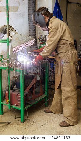 Sculptor welding a metal piece
