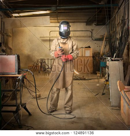 Sculptor holding welder in a workshop