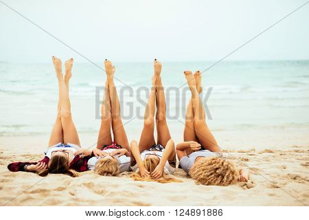 Attractive women lying down on the beach and putting their feet up.