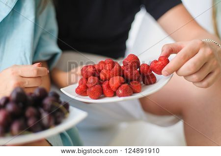 Man and woman eating Strawberry and cherry. Large tasty strawberries on a white plate. Cherries on a plate blurred. Man holding a strawberry. Guy hugging girlfriend and gives her strawberries.