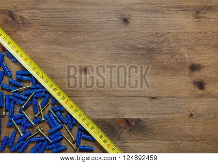screws with blue dowels tape measure, meter on old wooden table