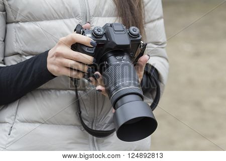 girl with beautiful manicure holds single-lens reflex camera