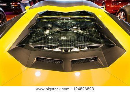 Verona, Italy - March 15, 2015: Transparent rear window with rear engine view of a yellow sports car.