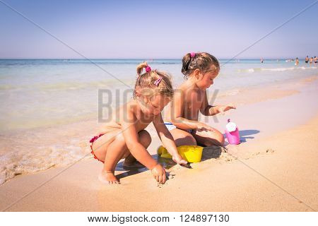 Two little girls playing with sand on the seashore.